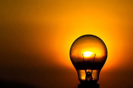 Close up light bulb with sunset sky background  photo