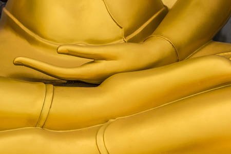 Close up golden hand of buddha statue in thai temple. photo