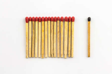 A series of  red matches are next to each other, which different black one   photo