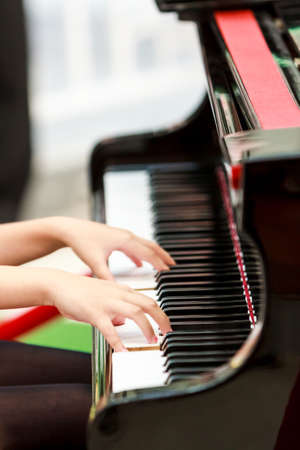 Close up of the hands of a young woman playing piano  photo