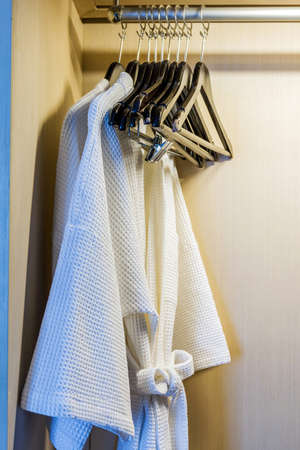 Close up of twins bathrobe in wardrobe in hotel. photo