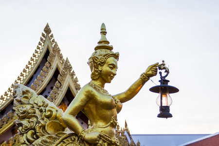 Goldent Ginnaree statue art holding a lamp,Thai temple,Thailand. photo