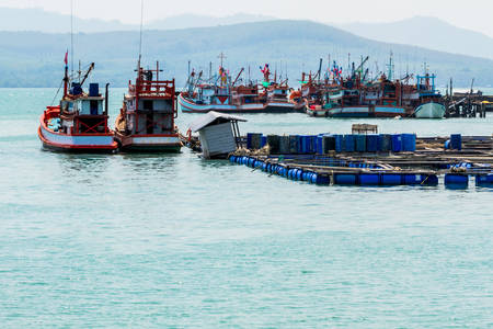 fish rearing: Cage aquaculture farming is done on coastline and nice fishing boat  prepares before a fishing,Thailand.