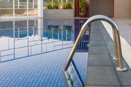 Reflection of water, Swimming pool with steel ladder bar in a sport club   photo