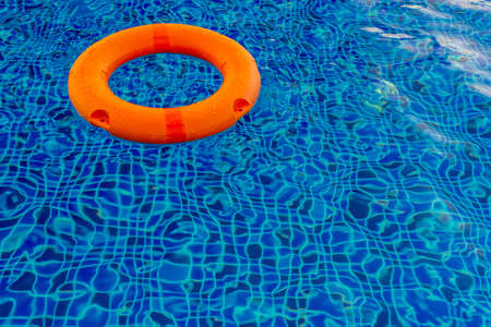 Swimming pool with pool ring, orange pool floatable toys in the blue water  Stock Photo