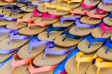 Colorful of rubber slippers for sale on the ground outdoor, no brandnames or copyright objects. photo