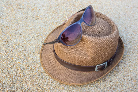 Woven hat with sunglasses on sand tropical beach. photo