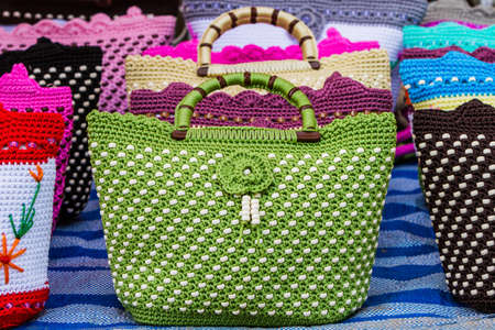 woman handle success: Colorful of vintage handbag for sale outdoor, no brand names or copyright objects.