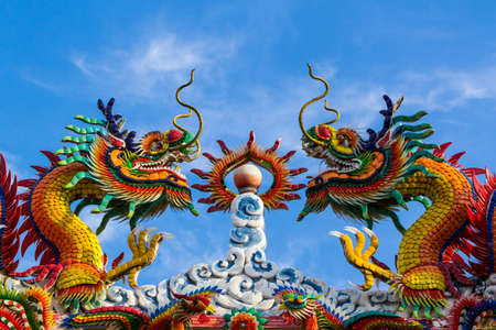 Colorful dragon on Chinese style roof decoration on blue sky background. photo