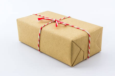 Cardboard carton wrapped with brown paper, tied with string.  photo