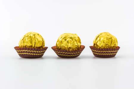 Sweet chocolate ball wrapped in golden foil isolated on white background. photo