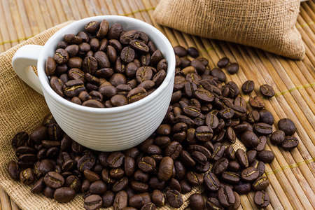 Brown roasted coffee beans in coffee cup on canvas sack   photo