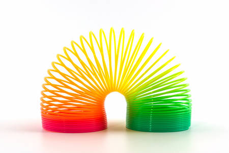 Rainbow colored wire spiral toy on white background. Stock Photo