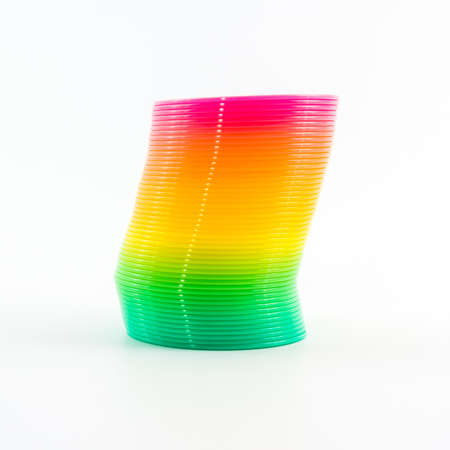 Rainbow colored wire spiral toy on white background  photo