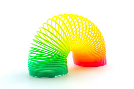 resilient: Rainbow colored wire spiral on white background.  Stock Photo