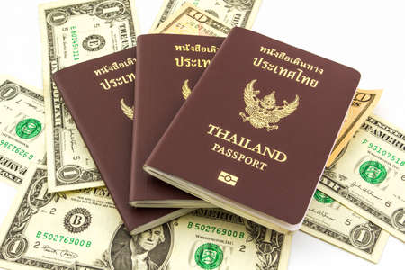 Thailand passport on U.S. Currency bank note on white background.  photo