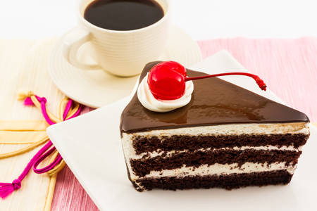 Chocolate cake slice with red cherry fruit and coffee cup .  photo