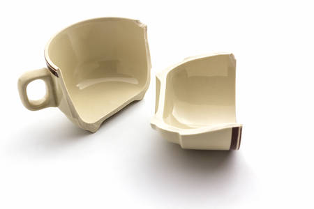 Broken coffee cups on white background. Imagens