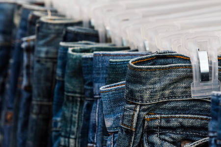 Row of Jeans and trousers on hangers for sale. photo