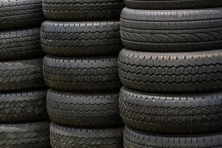 Stack of old wheel black tyres texture background. photo