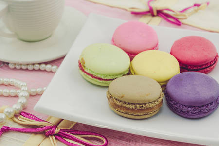 Vintage of Sweet french macaroons or macaron on white plate, Dessert. photo