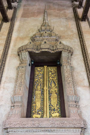 Ancient Gold carving wooden window of Laos temple