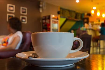 Sluit omhoog kop van koffie op lijst in koffie. Stockfoto