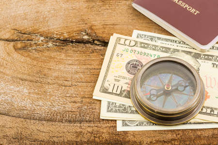 credential: Compass, passport and money on wood background.