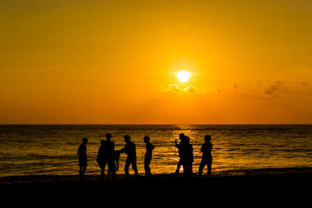 Silhouettes of young happy people enjoing sunset at the beach. photo