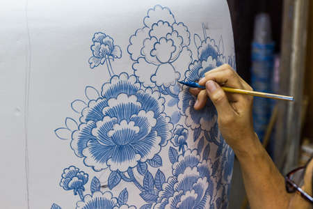 Hand met penseel schilderen een pot, handwerk. Stockfoto