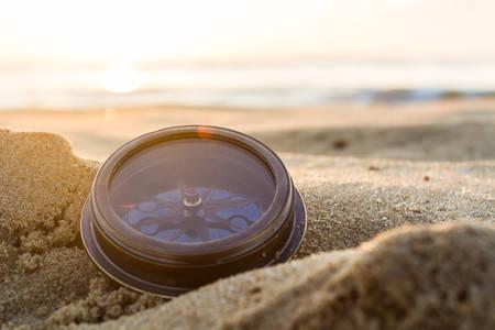 Oude kompas op het zand op het strand Sunrise, natuur achtergrond.