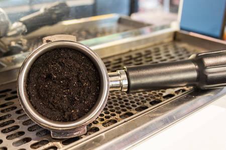 Close up Grounded espresso in a portafilter, coffee machine. photo