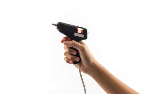 Electric hot glue gun holding on hand.