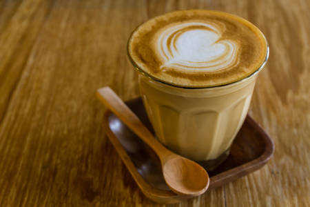 Cappuccino or latte coffee on wooden table in vintage tone style. photo