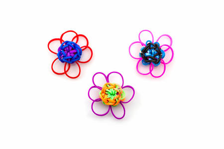 loom: Colorful elastic rainbow loom bands flower shaped on white background. Stock Photo