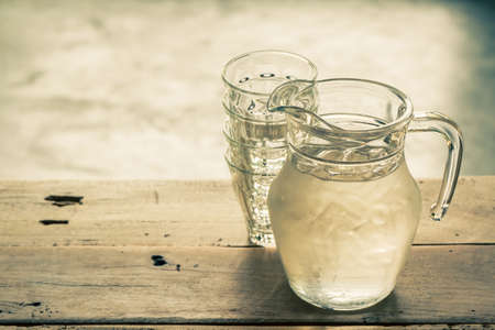 Glass pitcher of water and glass on wooden table background, vintage color tone. photo