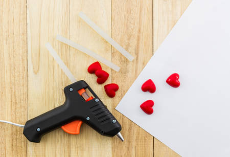 Closeup electric hot glue gun apply the glue to making postcard with red heart. Stock Photo