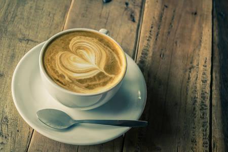 comida arabe: Cappuccino o latte café en la mesa de madera en estilo del tono de la vendimia. Foto de archivo