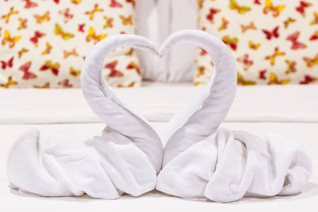 feel affection: Two swans heart shaped made from towels on honeymoon bed. Stock Photo