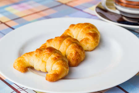 Breakfast with fresh delicious croissants on white plates