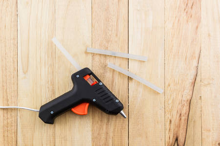 cohere: Electric hot glue gun on a wood background.