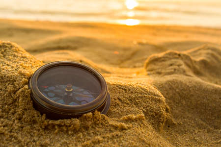 Ancient compass on the sand at the Beach Sunrise ,nature background .