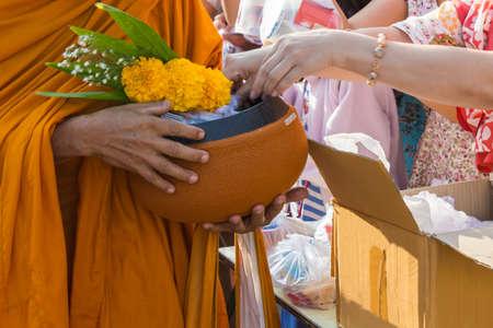 limosna: Monje budista, mientras que de pie en una fila esperando personas ponen ofrendas de arroz en su tazón de limosna para hacer méritos