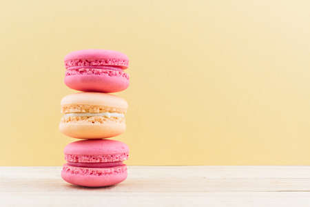 Sweet and colourful french macaroons or macaron on wood background, Dessert. photo