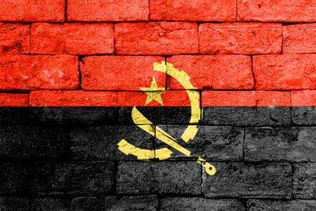 Flag of Angola painted over on old brick wall.