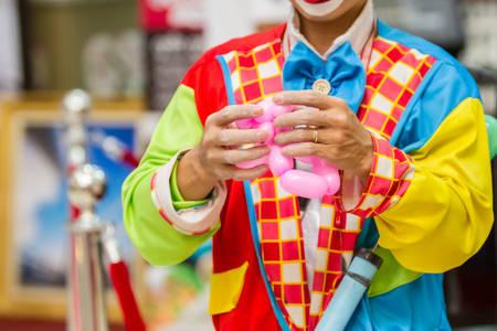 birthday clown: Funny birthday clown blows up a balloon to twist into an animal shape.