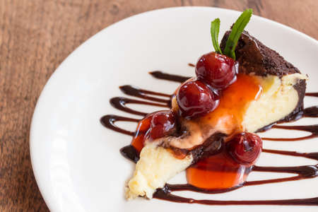 fruit plate: Chocolate brownie cheesecake with cherry fruit on white plate.