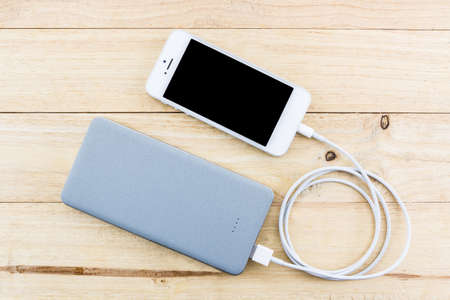 Smartphone with grey powerbank on wood desk.