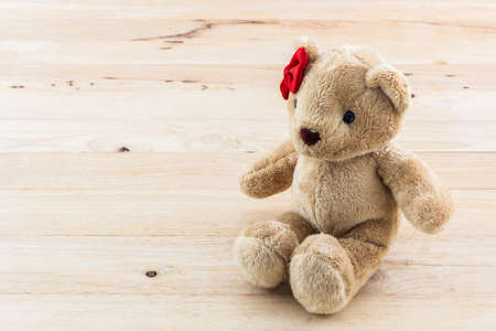 oso de peluche: Peluche clásico oso de juguete lazo rojo sobre fondo de madera. Foto de archivo