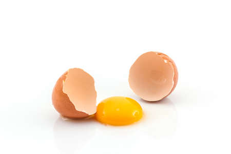 Cracked egg and shell on a white background. Broken chicken egg. Stock Photo